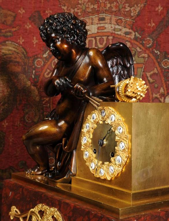 A large, fine and exquisite, early antique French clock depicting cupid holding a sharpened golden arrow. It is of stunning quality and fully serviced and tested by our clockmakers. It is of finest ormolu (finely gilded bronze or bronze doré)