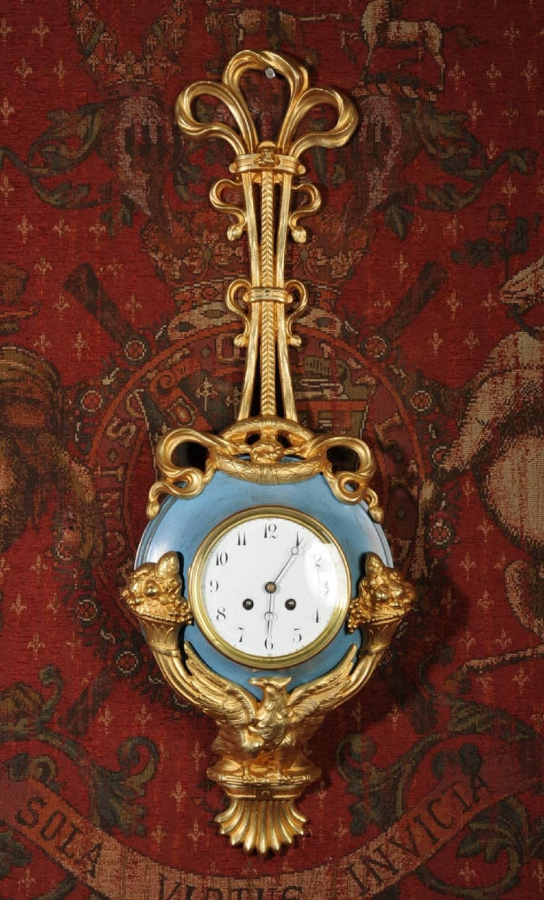 A large, unusual and very decorative original French antique Cartel wall clock. It is classical in design, hanging from a large gilt bronze bow with a laurel wreath. The clock is mounted in a toleware body with original blue painted finish. Below