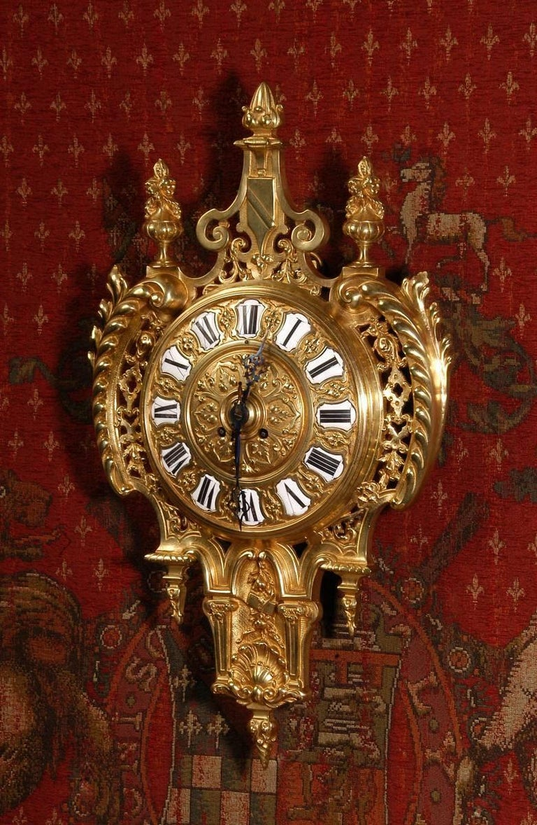A stunning Baroque style antique French Cartel wall clock. It is beautifully modelled in gilded bronze in the shape of a shield. To the sides are bold acanthus scrolls with finely fretted panels and to the top is a shield and a pair of urns. The