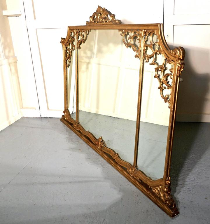 Very large 19th century Adams style gilt over mantel wall mirror  The mirror has a beautiful Rococo gold frame with three mirrors, at the top it is elaborately decorated with carved swags of leaves and Ribbons and a crest at the centre. The base
