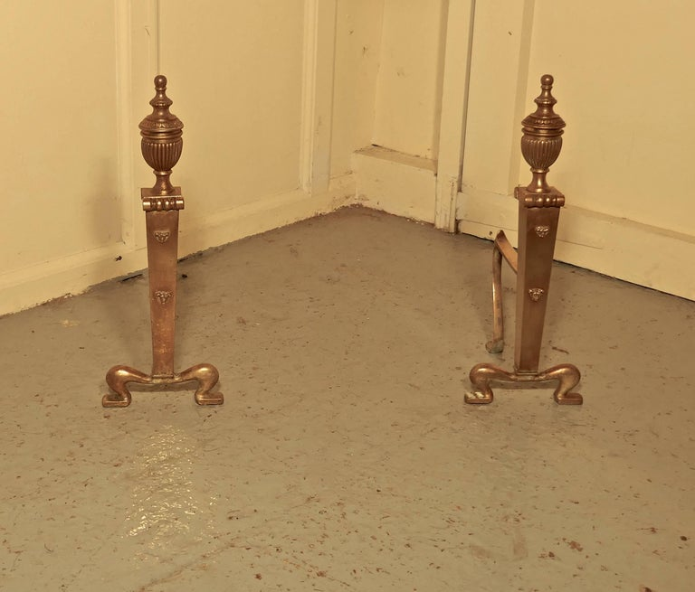 """An elegant pair of 19th century brass andirons or fire dogs  This very attractive pair of brass andirons, they have a classical look with tall urns on the top and attractive scrolling feet  The andirons are measure: 17"""" high, 16"""" long and 9"""""""
