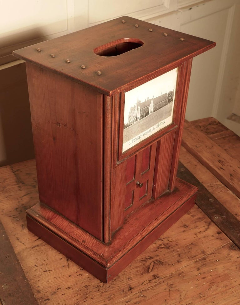 Victorian school house letter box, post box.  The post box is a very attractive piece, it has a slot in the top for letters and a picture of St Georges School Harpenden on the front above a pretty little four-panel door which has red leather in