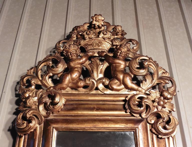 This is the most impressive mirror, a charming piece, dating from 1780. The glass is set in a deep moulded frame which is crowned with cherubs holding a basket of flowers, the flower theme is repeated at the upper corners and the centre bottom of