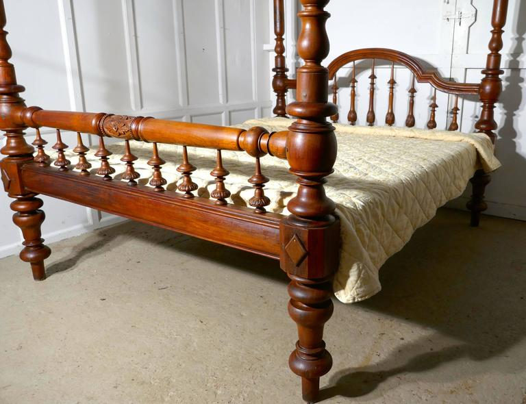 This is a superior quality piece, the bed originates from India often know as a Raj bed, the bed is handmade, it is a four poster with carved turnings and is unusually, a light colour polished wood  The head of the bed has a pleasant arched shape