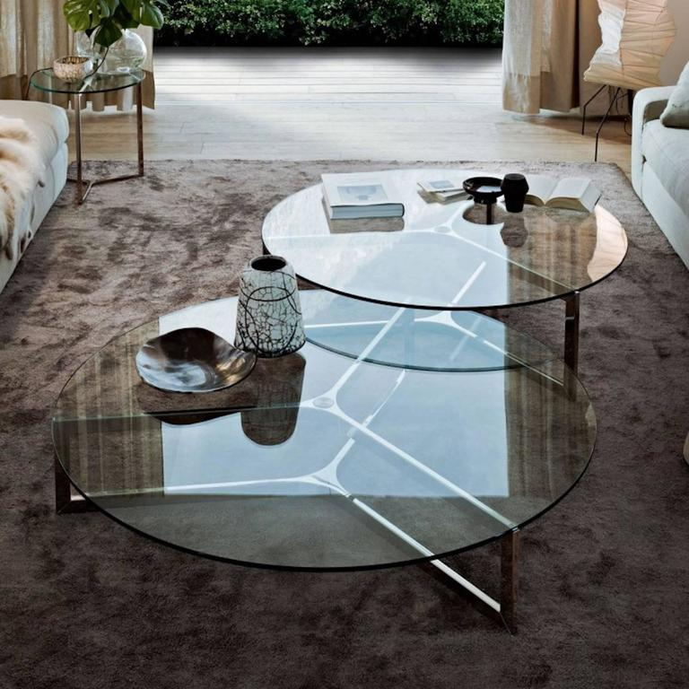 "Side or coffee table with 10mm transparent glass top. Bright stainless steel base. Chromed aluminium central part. Available also with smoked ""grigio Italia"" glass top and burnished metal structure.
