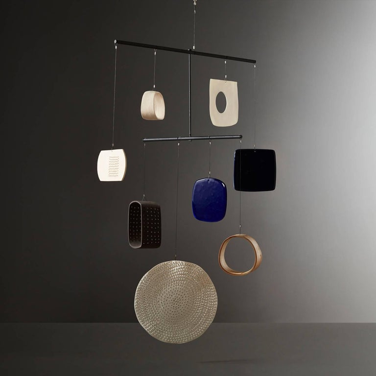 Daniel Reynolds' navy and apothecary blue mobile is a large handmade mobile, composed of a gourd section, porcelain, stoneware, and glass shapes in varying hues. Adhering to a simple colour palette of black, white, blue and cream Daniel Reynold's
