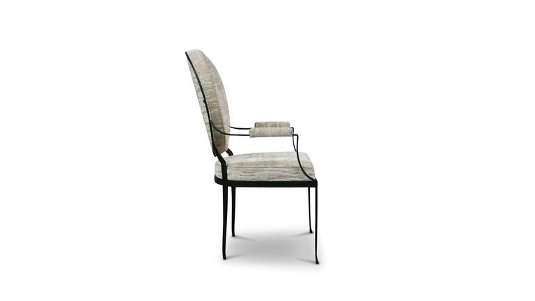 The andre chair features a hand-forged, blackened iron frame with a gentle-curving back and arms. It is informed by early 20th century French design and made to order in any leather or fabric. Also available without arms.