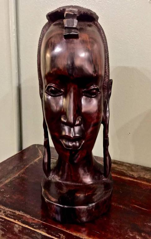 This is a stunningly beautiful African carved ebony female bust. The figure has been carved from a solid ebony trunk; the fine carving of this very dense wood reveals the skill of the carver who has chosen to highlight the deep graining of this
