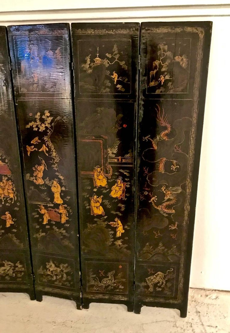 This is an unusual and wonderful example of an 18th century Chinese lacquer table screen. The ten-panel screen is double-sided showing painted scenes of an Imperial figure to the front side with figures highlighted in gold; the reverse features