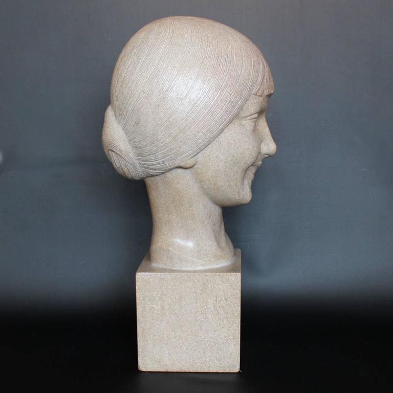 An Art Deco, stone carved sculpture of a smiling young lady, set over an integral plinth. Original dedication plaque to rear.