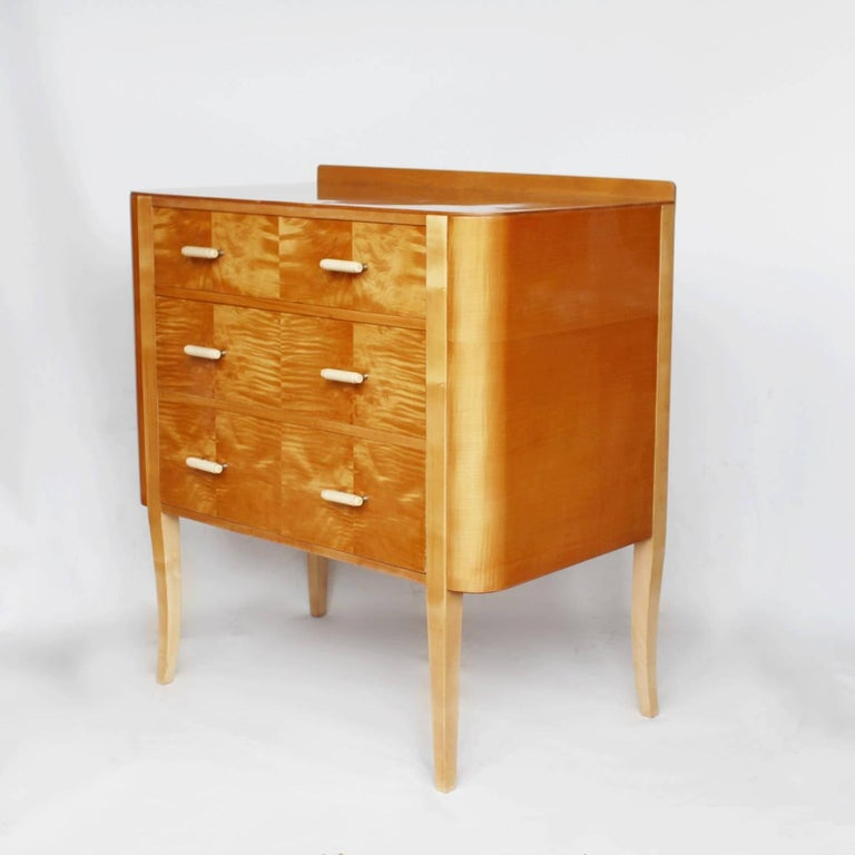 An Art Deco chest of drawers in figured satin birch with stepped ivorine and metal handles. Raised on tapering, sating birch legs.