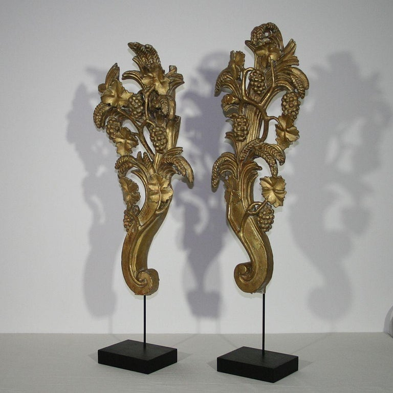 Unique and very beautiful three dimensional ornaments with traces of their original gilding. Richly decorated with grapes, wine leaves and grain. Original period pieces, Italy, circa 1750. Weathered, losses and old repairs.