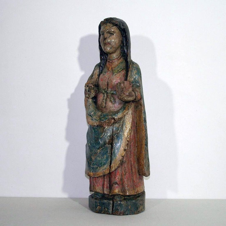 Unique and extremely rare medieval wooden Madonna with traces of her original color Original period piece, France circa 1500 or older Weathered, small losses.