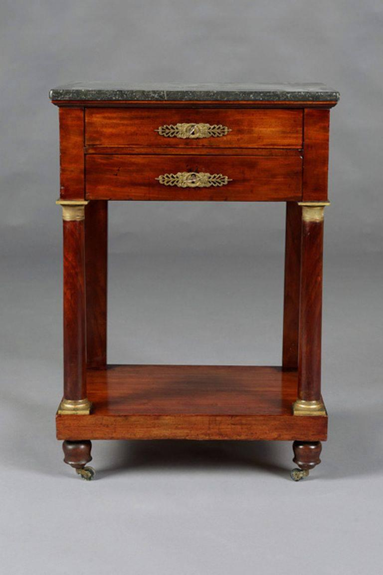 French Empire. Solid mahogany wood. Gilded and chiselled fittings. Two-wise frame base with protruding rectangular marble slab on square columns, joined by an intermediate compartment ending in rollers. Plate with beveled corners.   (G-54).
