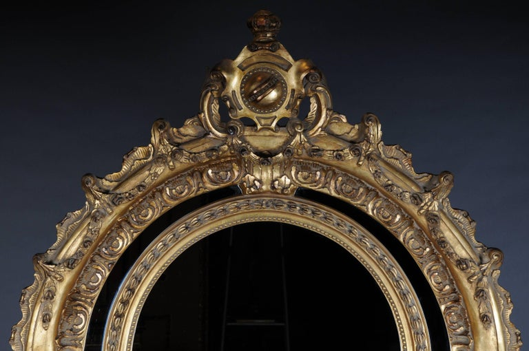 Solid beechwood, finely carved and gilded. Elaborately carved and strongly curled frame conclusion. High crest-shaped mirror frame. Rich gable-like openwork rocaille crowning.