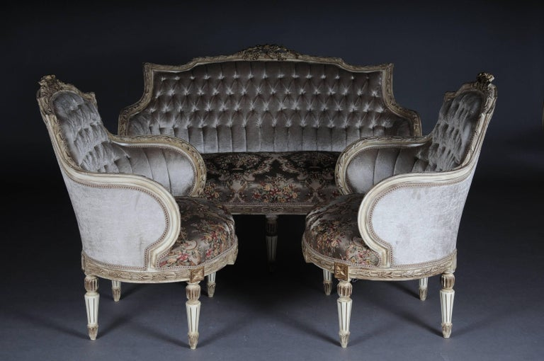 Solid beechwood, carved and partly gold-plated. Semicircular rising backrest framing with rocaille crowning. Profiled frame with richly decorated carving. Profiled frame on conical, fluted legs. Seat and backrest are finished with a historical,