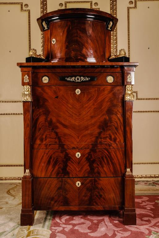 Cuba mahogany on solid oak and softwood partly ebonized. High-rise, architecturally designed corpus. In the front three drawers of different sizes. Straight writing board, behind it architectural interior life with secret pockets. Flanked by