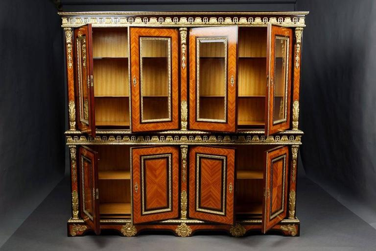 Imposing French Bibliotheque in Louis 14th style Solid beechwood, ebonized. Highly right angled body flanked with figures in the form of feminine masks on sweeping border. Frieze from acanthus leaves. Recessed fixtures from two glassed, wing- doors