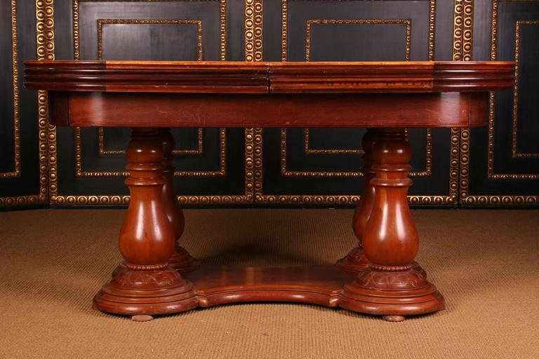 A monumental noble and rare extension table, circa 1850. Pyramids mahogany and solid walnut. The cambered frame is connected to four baluster-shaped columns below a wide corresponding storage compartment. This large extension table is characterized