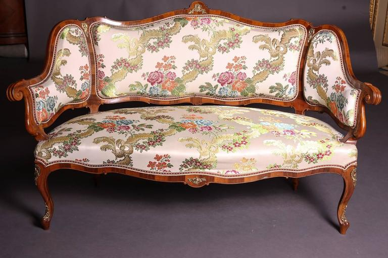 Four chairs with a sofa in Dresden baroque style. Walnut freed and felted. Rich gilded bronze appliqués, on the backs with perimeter bar contours. Saxony, circa 1880-1890.  Dimensions: Canapé: H 92 cm, W 149 cm, D 77 Chair: H 93 cm, W 45 cm, D