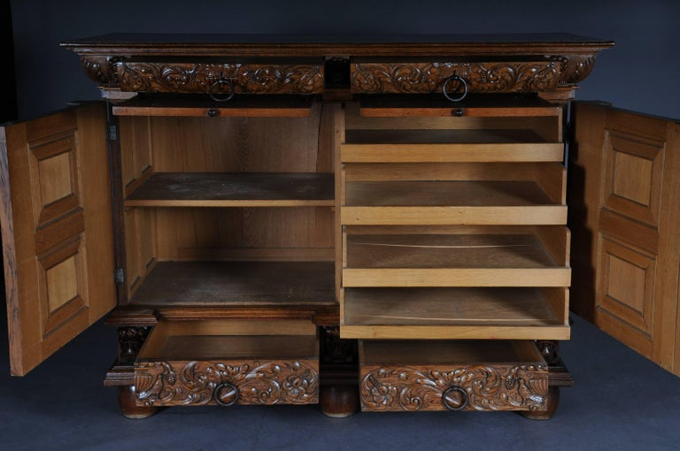 Oak, solid. A two-door casted base with four drawbacks and finely carved mascarons and acanthus leaves, laterally with plastic, meshed, ionic half-columns. Underneath the upper drawers, extendable dressing plates, circa 1890.   (O-232)
