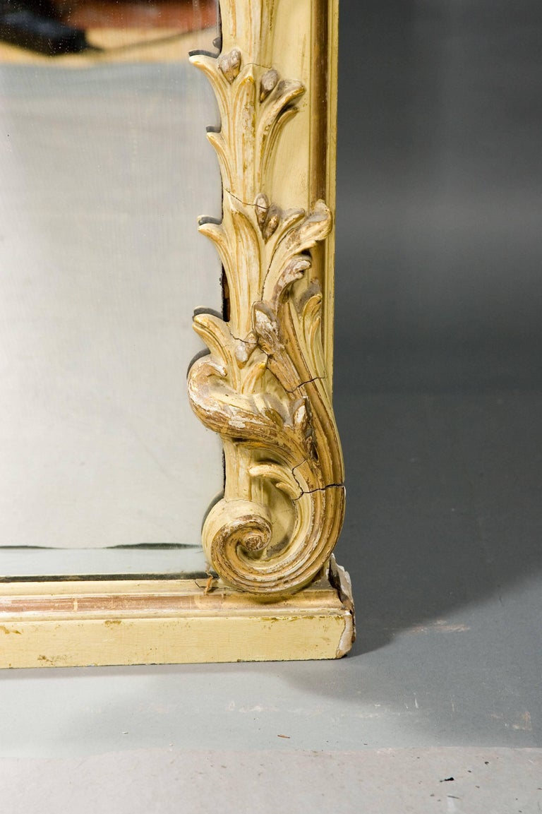 A monumental mirror in the Louis XVI style, circa 1850-1860. Wood and stucco. Poliment gilded and colored. High-angled mirror frame made from acanthus leaves surrounding the circumference. Fully embellished crown of rocaille cartouche and plastic