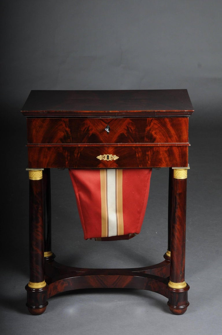 Solid oak, Cuba mahogany veneer. Fire-gilt fittings. Hinged cover plate with intermediate compartments. Slip-in drawer on four full columns with four fire-gilded capitals and bases.   (G-74).