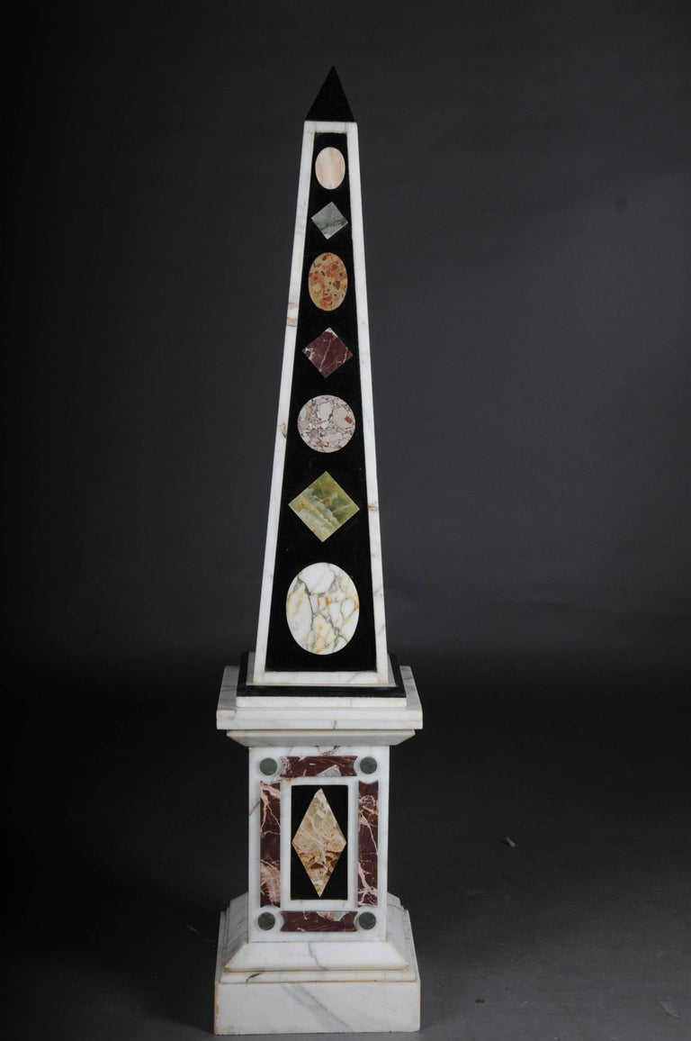 Extremely rare and decorative obelisk pair. Various types of marble an absolute rarity and a guaranteed eyecatcher in every interior. Measures: 73.2 inch.   (U-Hud-1).
