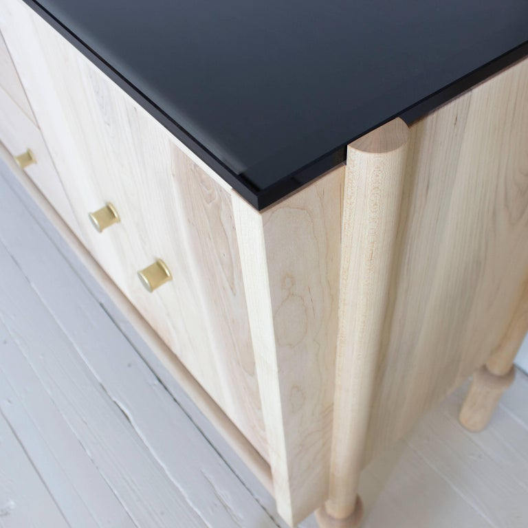 Solid wood case / hand turned legs / zero voc oil finish / solid brass pulls / 1/2 in glass top   Dimensions: 60