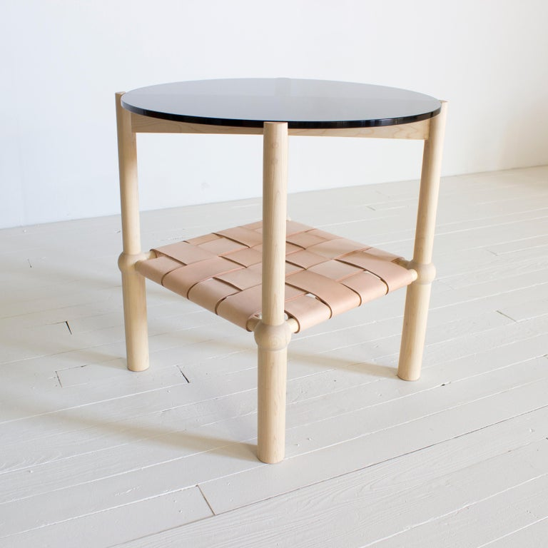 """Solid wood frame / hand-turned legs / zero voc oil finish / woven veg tanned leather / 1/2 in circular glass top   Dimensions: 24"""" W x 24"""" D x 24"""" H  Wood: Walnut, white oak, maple, blackened oak   Leather: Black, natural, brown   Glass:"""
