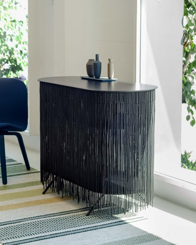 Keefer is a credenza that alludes to the objects stored within its shelves, yet obscures their identity through its bamboo-beaded skirt. The skirt masks the vertical supports, creating the illusion of floating shelves. The interior can be accessed