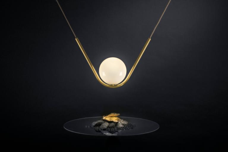 Perle 1 is a luxurious high-end lighting fixture that has been coated with warmth and elegance. Inspired by the romantic world of jewelry, the Perle collection is handcrafted with a delicate metallic structure and a 8'' hand blown glass ball as the