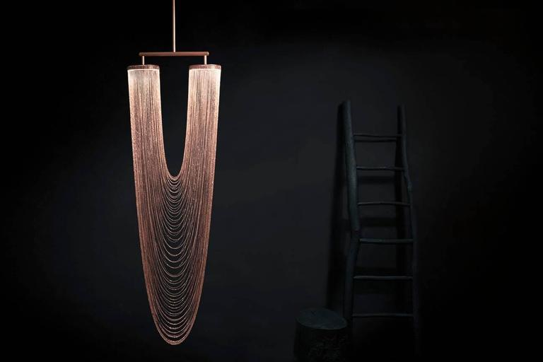 Otero is a luxurious high-end lighting fixture that has been coated with warmth and elegance. This sculptural light is handcrafted with delicate copper chains to create a unique and elegant curved shape inspired by the romantic world of jewelry. The