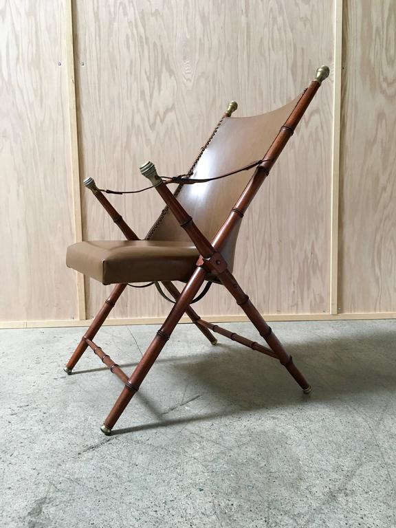 Faux bamboo campaign chair Mid-Century the strap is leather and the seat and back are vinyl.