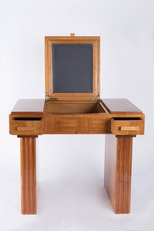 1930s lemonwood veneered French origin art-deco vanity. It can be used as well as a small desk . Top opening to a small cabinet, mirror inside of the top. Two drawers,one on each side. Wooden handles. Small shelves on both sides. Veneered and