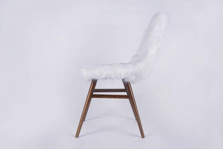 Burian Judit, Hungarian origin interior designer was inspired by the Scandinavian design of the 1950s. She designed the Erika chairs in 1959. A very elegant and comfortable model. The tinted ashwood frame and the beautiful white coloured faux long