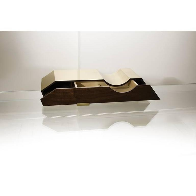 A truly modern and unique piece, this desk organizer is essentially a mobile drawer compartment in polished brass and hand varnished walnut. This organizer is designed to be either mounted on the wall or left freestanding, posed on a desk or table.
