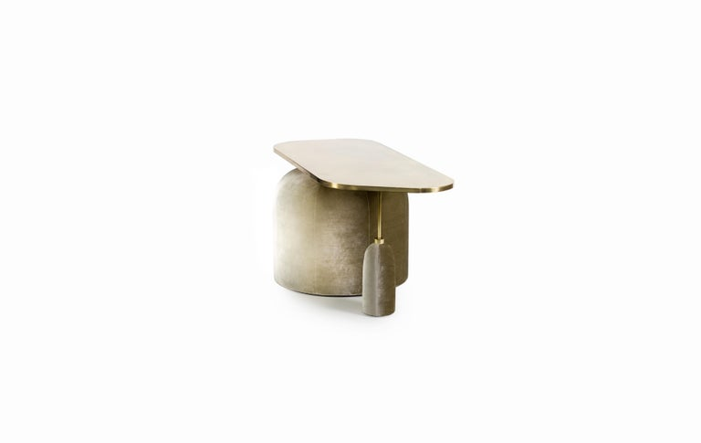 A truly unique collectible design piece which functions as a cocktail or side table with a pivot base visual aesthetic. The two base pieces are upholstered in a cotton velvet and the tabletop finish as pictured is a hand patinated brass. Various