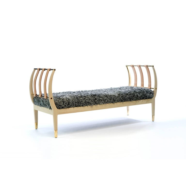 """Resembling the rib of a whale, this American ashwood bench is complemented by brass rods and archs of vegetable tanned leather straps that are hand-stitched in waxed linen thread and accented with """"x"""" type stitching. This bench can also be"""