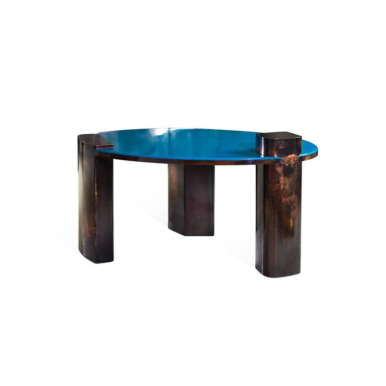 Blue coffee table is undeniably the most breath taking piece in the Moon Series collection. This copper table delights by the depth of its blue resin top and meticulous details of its hand patinated base. Limited edition of eight pieces. Galerie