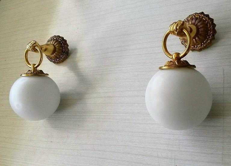 Charming pair of French neoclassical sconces in gilt bronze, in the style of the Maison Jansen. With nice white matte milky opaline globes. The electric part has been renewed, rewired and ready for the US standards (max 40 watts each