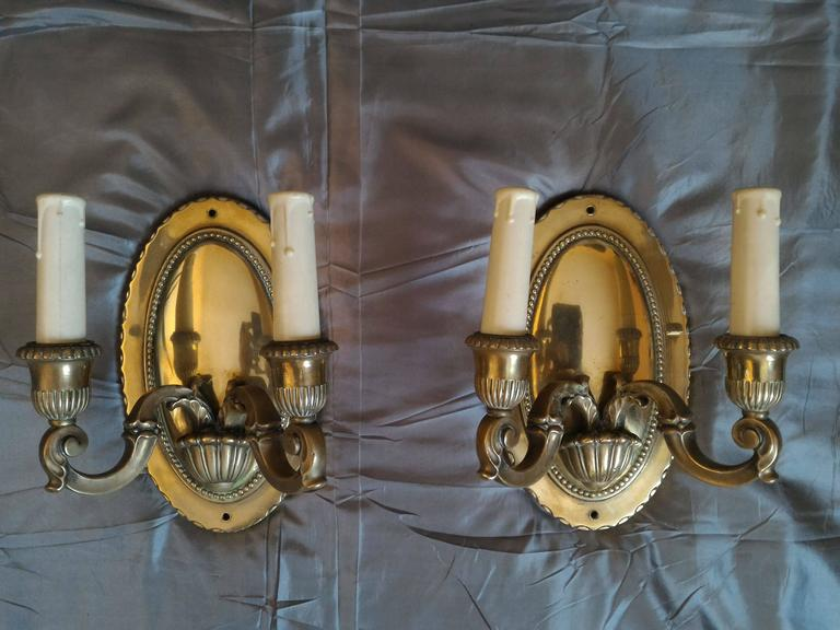 Pair of refined French gilt bronze two-arm sconces, bronze mirror reflection style that creates a gorgeous atmosphere.