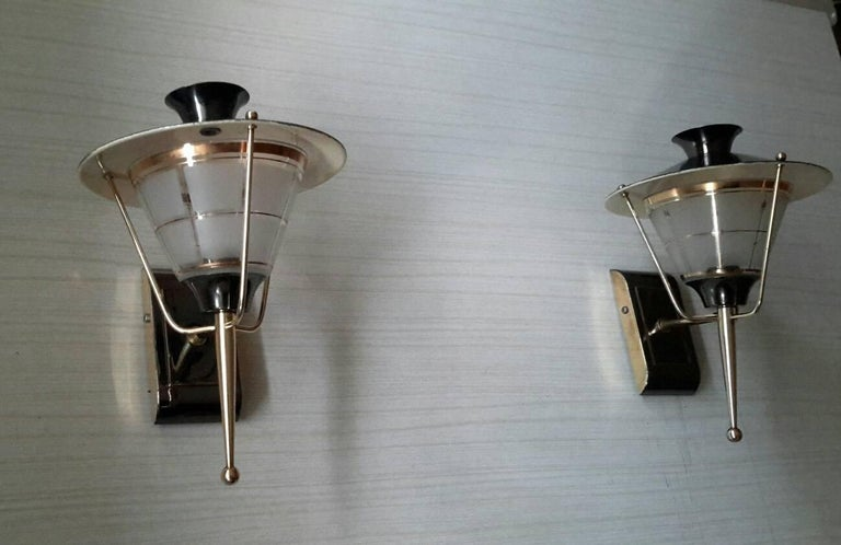 Very charming pair of French midcentury sconces lantern style in gilt brass and black llacquered patina, 1950s by LUNEL. 75 W max, excellent general state, electric part has been checked med and fits the US standards .  Dimensions :  H : 25