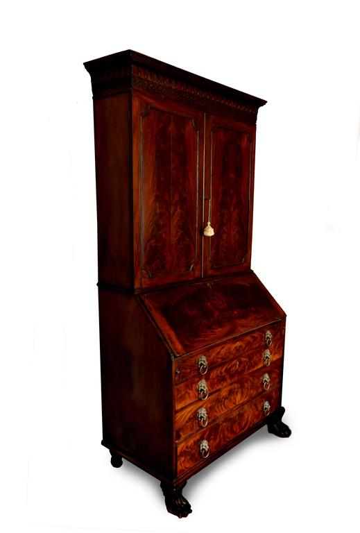 Magnificent flame mahogany secretary. The cornice of the piece features fine dentils, gothic arches, and delicate blind fretwork. The upper two doors of paired veneer open to sets of original shelves with adjustable supports. The matchbook veneer