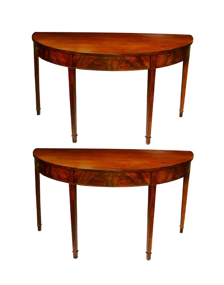 A lovely pair of American console tables in honey colored mahogany. The two demilune feature a graceful elliptical shape with flame mahogany veneer on the frieze and crossbanding of holly and mahogany. The tabletops are composed of single