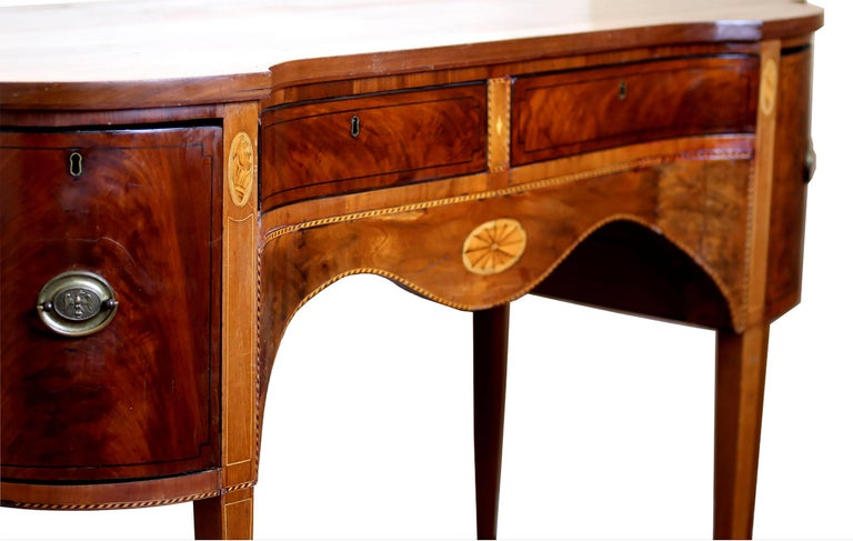 Striking sideboard buffet with concave center in mahogany, satinwood, holly, and ebony. Center section contains silver and linen drawers while outer deep drawers housed liquor and wine cooler. Banded inlay throughout with conch and central spider