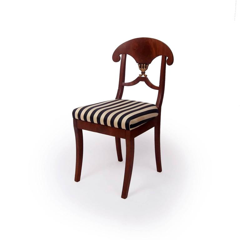 Pair of regal side chairs with Napoleon Hat crest rails, parcel-gilt trident detail in splat, square saber legs, original drop seats upholstered in striped black and cream upholstery. Biedermeier style from Sweden, circa 1825.