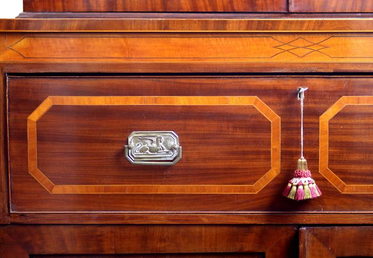 Exquisite, singularly unique Hepplewhite secretary bookcase in mahogany, satinwood, and boxwood. The cornice exhibits urns and panels, and the center is punctuated by octagonal panel surmounted by a segmented arch with Adamesque spiderweb inlay. The