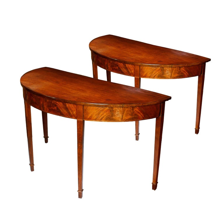 A lovely pair of American console tables in honey colored mahogany.  The two demilunes feature a graceful elliptical shape with flame mahogany veneer on the frieze and cross banding of holly and mahogany.  The tabletops are composed of single