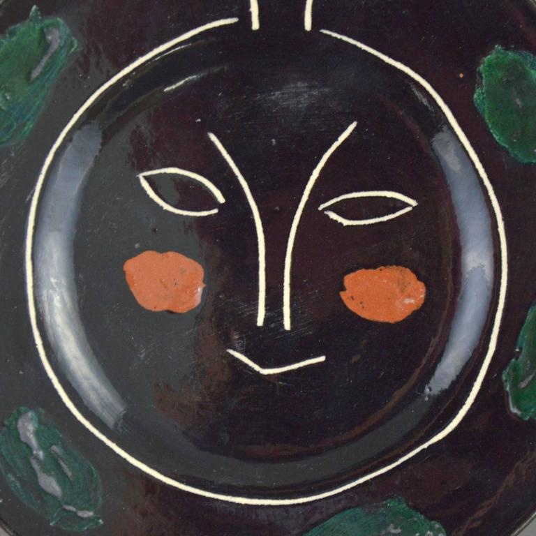 Pablo Picasso ceramic plate black face - Plate J. White earthenware clay, knife engraved underglaze and engobes decoration. Executed in an edition of 100 copies. Stamped and marked 'R/Madoura Plein Feu/D'Apres Picasso'. Conceived in 1948.